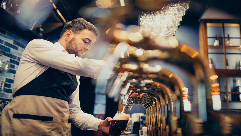 Holiday Inn Calais Coquelles - handsome-bartender-pouring-beer-in-pub.jpg